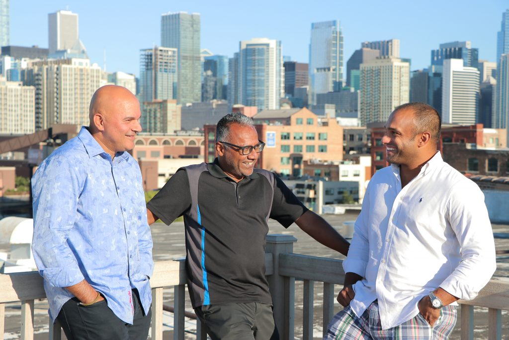Beyond Academics Leaders (from left to right) Joe Abraham, Matthew Alex, and Joel Mathew Smiling in Front of Chicago Skyline